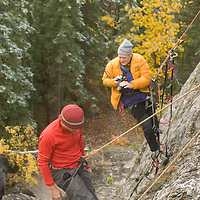 Photographer shoots rock climber on Rundle Rock near town of Banff in Alberta's Banff National Park, Canada.