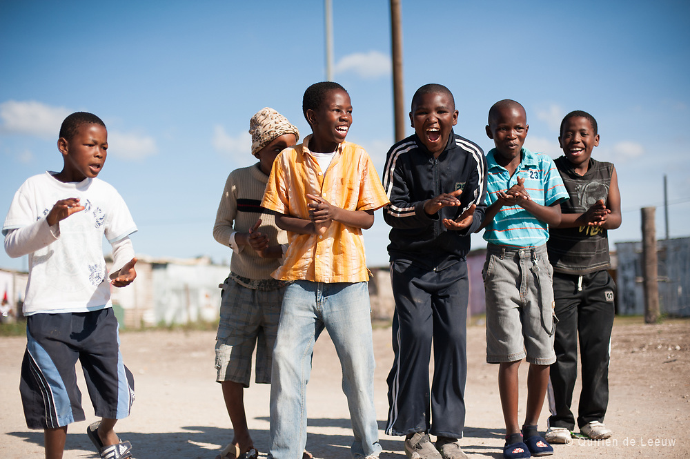 Children welcome new visitors with a dance in a local township