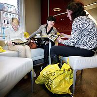 Nederland, Amsterdam , 1 oktober 2009..Bezoekers tijdens de eerste koopjesdag van de Drie Dwaze Dagen in warenhuis de Bijenkorf bekijken de aanbiedingen tijdens een kopje koffie in de restauratie tussen het winkelen door..Three Crazy Days, annual sale of the Bijenkorf store, promoting bargains.