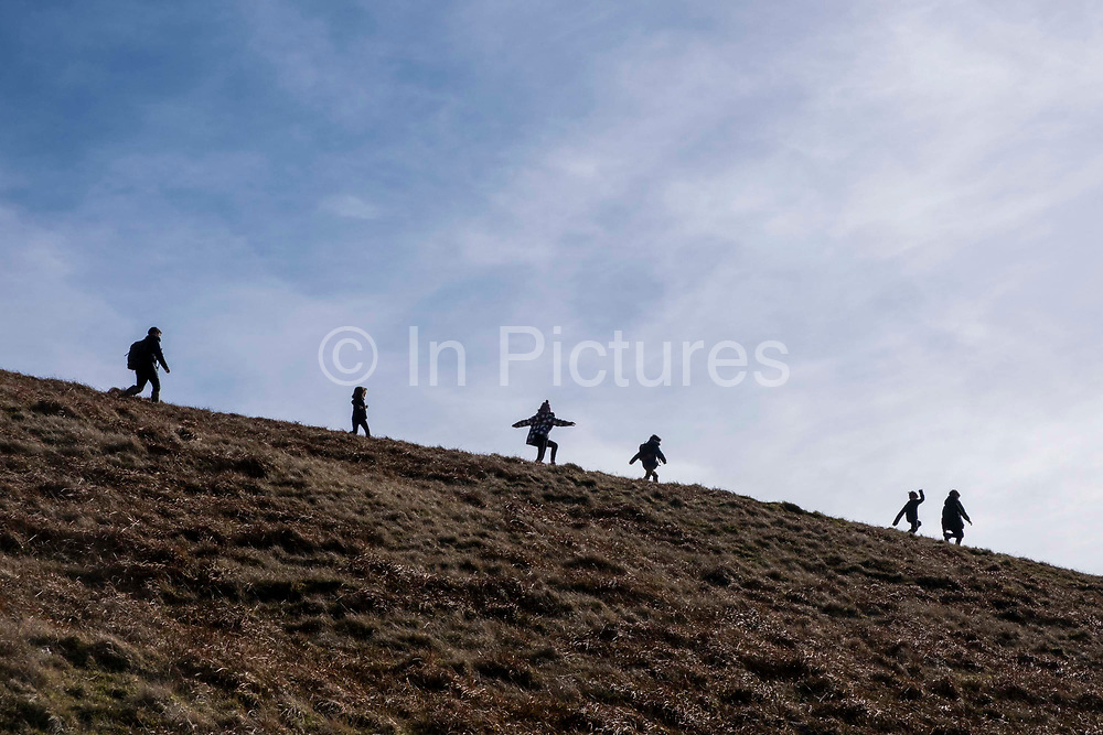 Silhouette of children playing, walking and running along the mountainside of Pen Y Fan in Brecon Beacons National Park, Wales, Powys, United Kingdom, chased by an adult.  Pen Y Fan is the highest point in the Brecon Beacons hill and mountain range in South Wales. The National Park was established in 1957 due to the spectacular landscape which is rich in natural beauty and is run by the National Trust.