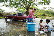 A woman and her daughter clean dishes in the river while others wash their pick-up truck in San Esteban, Honduras on Thursday April 25, 2013.