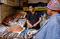 FEZ, MOROCCO - CIRCA APRIL 2017:  Moroccan fish seller and customer at the Medina in Fez