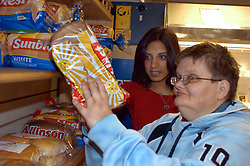 Support worker goes shopping with resident with learning disability from a sheltered housing scheme; Yorkshire UK