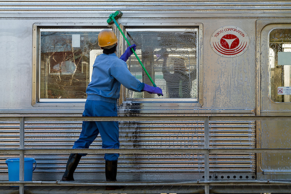 Cleaners wash carriages on the Tokyu Den-en-toshi Line at the Tokyu train yard in Tsukushino, Tokyo, Japan Saturday December 27th 2014