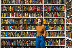 "© Licensed to London News Pictures. 24/07/2020. LONDON, UK. A Tate staff member wearing a facemask poses next to ""The British Library"", 2014, Yinka Shonibare CBE. Press preview ahead of the reopening of Tate Modern on 27 July after the easing of coronavirus pandemic lockdown restrictions by the UK government.  Visitors will need to book timed tickets online and follow one-way routes around the gallery space along with observing social distancing rules.  Photo credit: Stephen Chung/LNP"