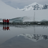 Tourists explore a cove at Damoy Point on Wiencke Island, Antarctica. In the far background are peaks of the Wall Range.