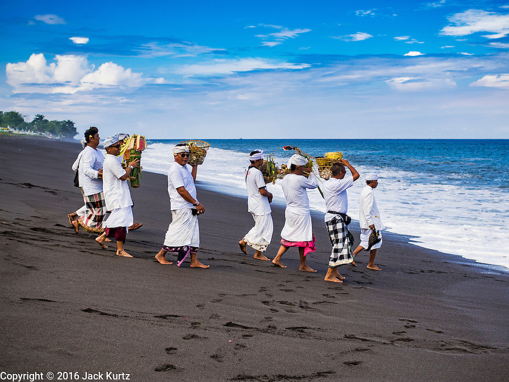 20 JULY 2016 - KUSAMBA, BALI, INDONESIA:   Balinese Hindu community leaders walk to the ocean to throw an offering into the ocean after a prayer service. Several hundred Balinese Hindus gathered on the beach in Kusamba, Bali, for a ceremony to honor the full moon. They prayed for more than hour and then community leaders threw an offering into the ocean.      PHOTO BY JACK KURTZ