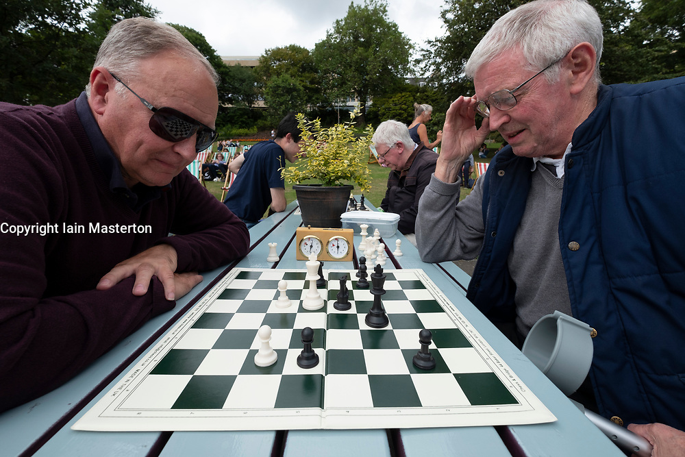 Edinburgh, Scotland, UK. 2 August, 2108. Public chess games in cafe in Princes Street Gardens. James Ferguson (L) and Dennis Anderson play chess on tables provided for the public and local chess clubs. They meet every Thursday and Sunday in summer.
