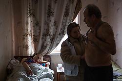 Doctor Svetlana Niekurasa (c) performs a checkup on Ivan Vorobyeva, 74, who looks after his frail wife alone.