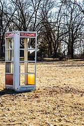 Abandoned phone booth sitting in a front yard in rural Illinois