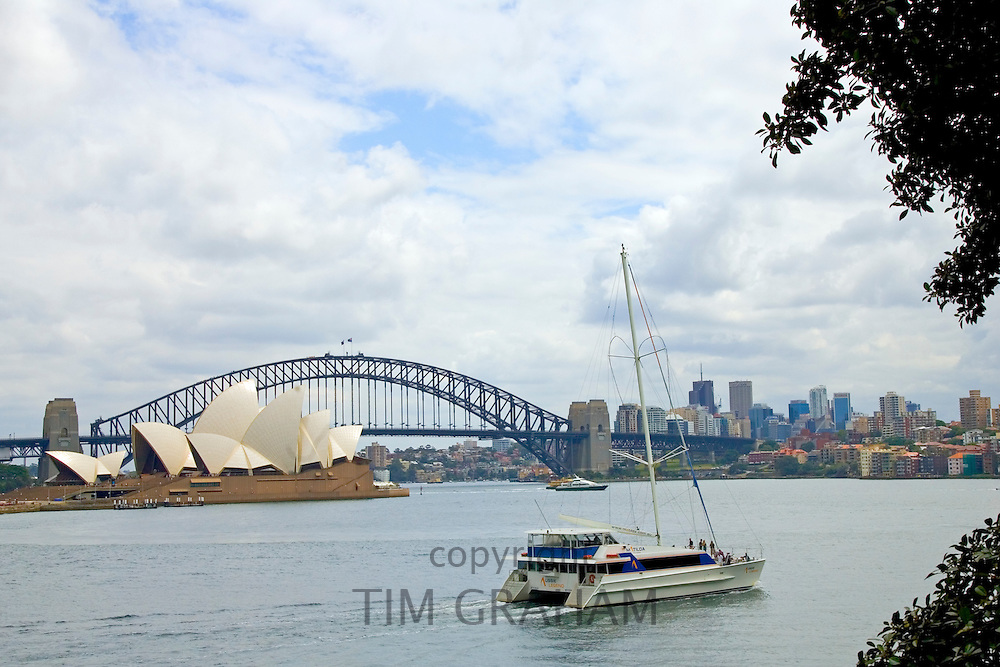 Sail boat passes by Sydney Opera House and Sydney Harbour Bridge, Australia