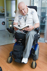 Male wheelchair user at home reading a book,
