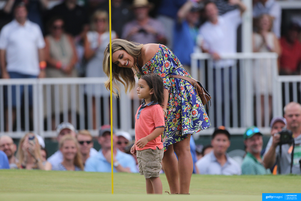 Dash, son of Jason Day, Australia, checks the hole on the final green watched by his mum Ellie after Jason Day  won the The Barclays Golf Tournament by six shots at The Plainfield Country Club, Edison, New Jersey, USA. 30th August 2015. Photo Tim Clayton