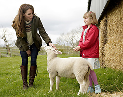 The Duchess of Cambridge strokes a lamb with farmers daughter Clover Chapman 9, during a visit to Manor Farm in Little Stainton, Durham. Picture date: Tuesday April 27, 2021.