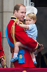 © London News Pictures. 13/06/2015. London, UK. Prince George of Cambridge being held up by his father Prince William.  Members of the Royal Family on the balcony of Buckingham Palace during the annual Trooping the Colour Ceremony in central London. The event marks the queens official birthday. .Photo credit: Ben Cawthra/LNP