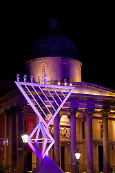 © Licensed to London News Pictures. 10/12/2012. London, UK. Britain's largest Hanukkah menorah is seen in front of the National Gallery after being lit in Trafalgar Square this evening (10/12/12). The Menorah, lit as part of the Jewish Hanukkah celebration will be on display until the Sunday the 16th of December. Photo credit: Matt Cetti-Roberts/LNP