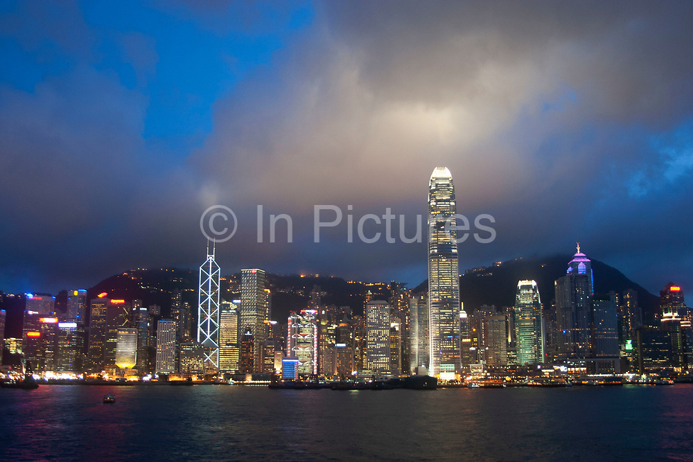 Clouds form over the peak at sunset and collect over Hong Kong's dramatic night skyline in Hong Kong, China. Many of Hong Kong's distinctive buildings line up including the once dominant Bank of China building. Two International Finance Centre now towers over the skyline at 88 stories 415m tall, lighting up the clouds it nearly reaches. A classic deep blue Hong Kong sky forms a backdrop for the forming clouds.