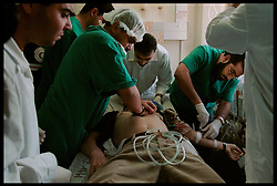 Doctors at Shifa Hospital in Gaza City, try in vein to save Rami Yassin, 17, the victim of bullet wounds to his throat and chest, which he recieved during a clash with Israeli soldiers Friday afternoon. Yaseen was pronounced dead moments later. (Photo © Jock Fistick)