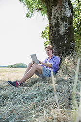 Mid adult man sitting under tree and using digital tablet