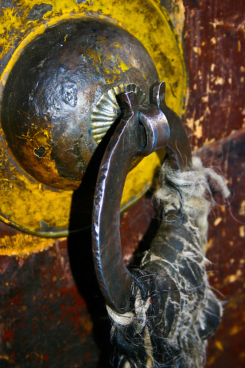 In an old monastery in Lhasa Tibet, this is a very heavy metal door handle wrapped with leather and yak hair ornament