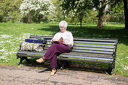 © Licensed to London News Pictures. 12/05/2016. LONDON, UK.  A woman sits on a bench reading a book during warm sunny weather in Green Park at lunchtime.  Photo credit: Vickie Flores/LNP