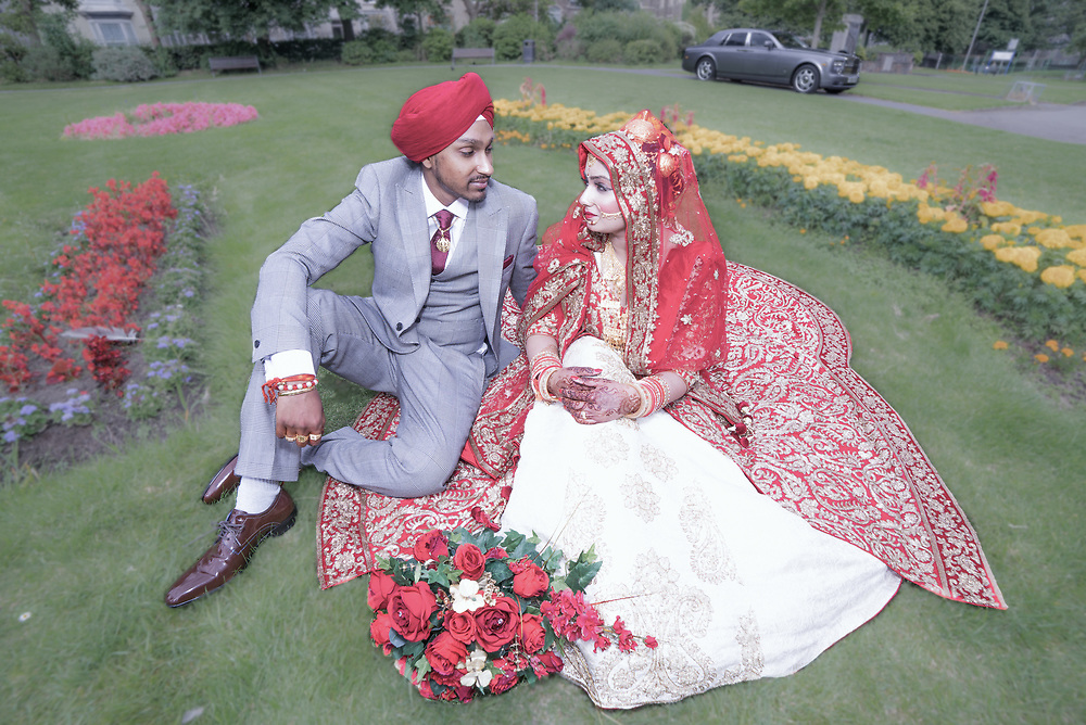 Sikh Punjabi bride and groom sitting on grass with rolls royce in the background