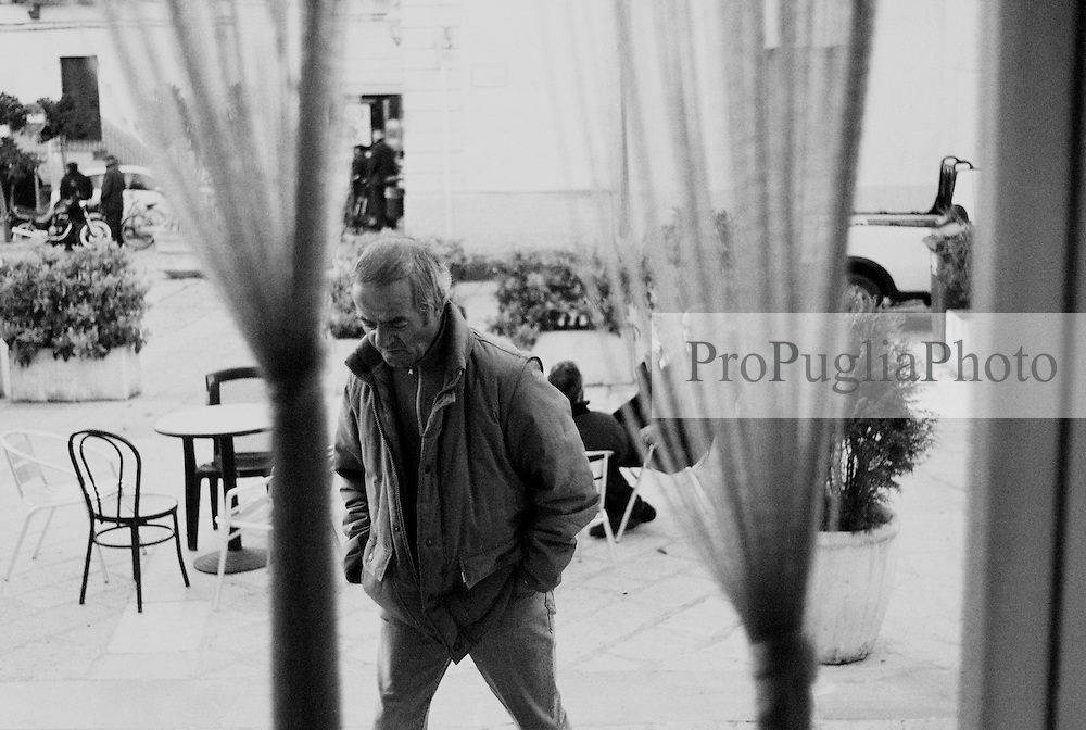Reportage sviluppato ad Alessano (LE). Viene presa in considerazione fotograficamente, la gente che popola il paese nei suoi bar, piazze, strade, giardini pubblici. Ed, insieme a questa, i particolari caratterizzanti il luogo...uomo entra in un bar