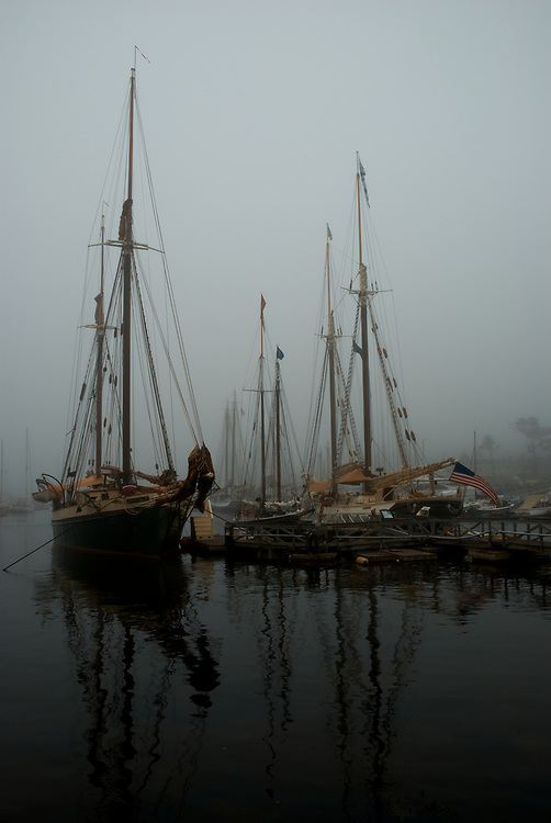 Subject: Schooners in fog       Image: A half dozen schooners lie fogbound in the harbor in Camden, Maine, hulls and rigging reflecting in dark waters. But for a few tell-tale modern giveaways, one can imagine this scene 100 years ago.