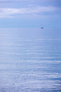View of sailing boat on the Adriatic sea with horizon over water, Trieste, Italy