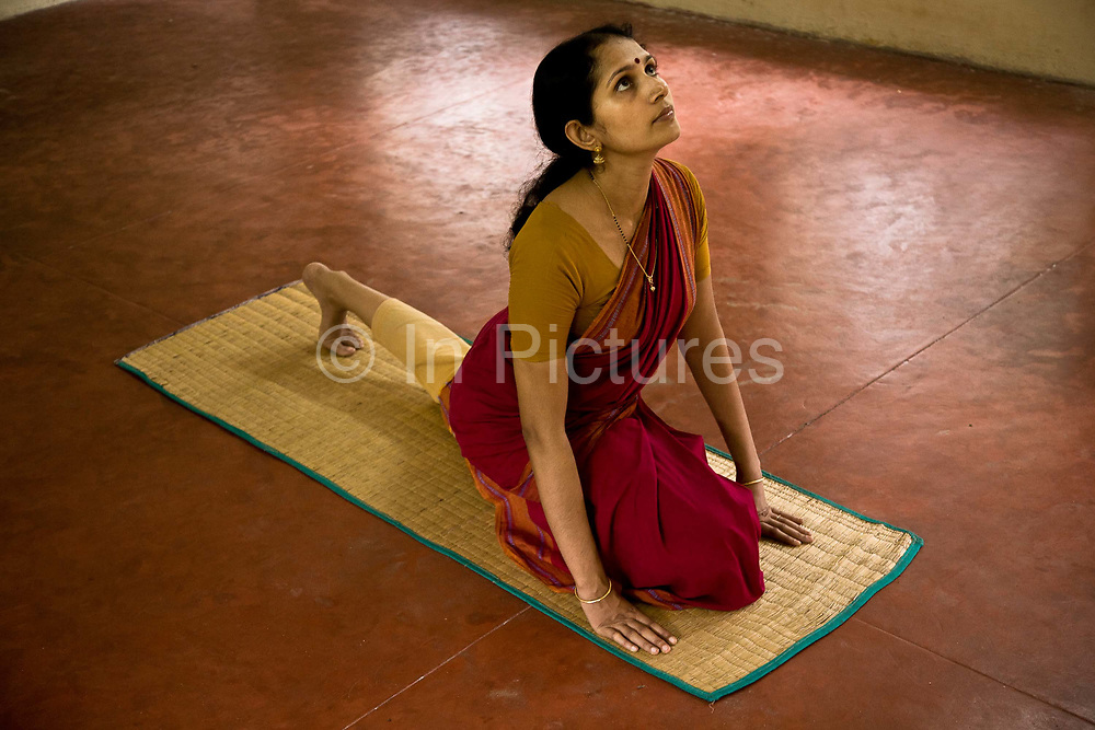 """Ganga Thampi a classical dance performer and teacher in a quiet moment of meditative yoga before a lesson at the highly prestigious Kalakshetra school for the arts, Chennai. The school was founded in 1936 and due to its exacting and demanding schedule is considered India's formost classical dance academy of this ancient cultural art heritage that is informally known as """"temple dancing"""" and that dates back to the Natya Shastra, the 2000 year old text that lays down the principles of Indian dramatic theory and performance. Tamil Nadu, India."""