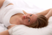 Smiling woman wearing white tank top laying on her back and relaxing in bed