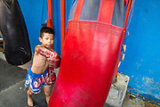 23 DECEMBER 2014 - BANGKOK, THAILAND: A boy works a heavy bag in the Kanisorn gym in Bangkok. The Kanisorn boxing gym is a small gym along the Wong Wian Yai - Samut Sakhon train tracks. Young people from the nearby communities come to the gym to learn Thai boxing. Muay Thai (Muai Thai) is a mixed martial art developed in Thailand. Muay Thai became widespread internationally in the twentieth century, when Thai boxers defeated other well known boxers. A professional league is governed by the World Muay Thai Council. Muay Thai is frequently seen as a way out of poverty for young Thais. Muay Thai professionals and champions are often celebrities in Thailand.     PHOTO BY JACK KURTZ