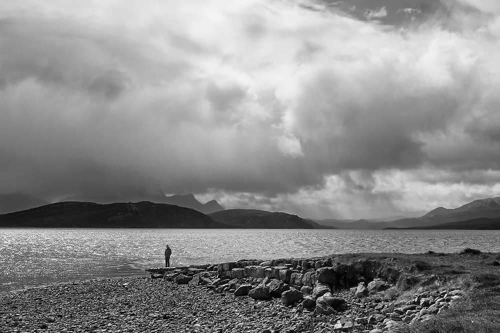 One man, one epic view across the Kyle of Tongue. A storm brews in the distance across the hills as he takes a moment to stand & contemplate.<br /> <br /> Photo by Jonathan J Fussell, COPYRIGHT 2021