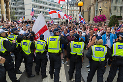 """Police use batons to deter angry protesters as they try to escape their pen on Langham Place to attack anti-fascist counter protesters nearby during a demonstration in central London demanding the release of """"political prisoner"""" right wing talisman Stephen Yaxley-Lennon  - also known as Tommy Robinson, who was imprisoned for contempt of court. London, August 03 2019."""