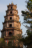 """Thien Mụ Pagoda is a historic temple in Hue, Vietnam. The pagoda has seven storeys and is often the subject of folk rhymes about Hue.  It is regarded as the symbol or icon image of Hue.   The pagoda sits on the Ha Khe Hill and sits on the bank of the Perfume River.   Built in 1601 by order of Nguyen Hoang the de facto independent ruler of central Vietnam.  According to the royal annals, Hoang while touring the vicinity, was told of the local legend in which an old lady, known as Thien Mu """"celestial lady"""" who foretold that a lord would come and erect a pagoda on the hill to pray for the country's prosperity.  After hearing this, Hoang ordered the construction of a temple at the site, thus the beginning of Thien Mu."""