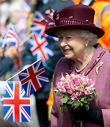 © London News Pictures. 30/04/2012. London, UK. HRH The Queen Elizabeth II receiving flowers while on a walk from Windsor Castle to the Guildhall, Windsor, Berkshire on April 30, 2012, where she attended a Diamond Jubilee reception. Photo credit : Ben Cawthra /LNP