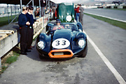 """Blurry photo of British Sports racing driver Bill de Selincourt (1921-2014) driving Lister-Jaguar """" Knobbly"""" car, BARC event Goodwood, March 1961 in pits"""