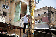 A man works on fixing the electricity in a street outside Shatila camp. The wirering in and aroundthe camp is very makeshift and DIY.