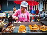 24 NOVEMBER 2015 - BANGKOK, THAILAND:  A street food vendor makes Thai style desert snacks at the Wat Saket temple fair. Wat Saket is on a man-made hill in the historic section of Bangkok. The temple has golden spire that is 260 feet high which was the highest point in Bangkok for more than 100 years. The temple construction began in the 1800s in the reign of King Rama III and was completed in the reign of King Rama IV. The annual temple fair is held on the 12th lunar month, for nine days around the November full moon. During the fair a red cloth (reminiscent of a monk's robe) is placed around the Golden Mount while the temple grounds hosts Thai traditional theatre, food stalls and traditional shows.       PHOTO BY JACK KURTZ