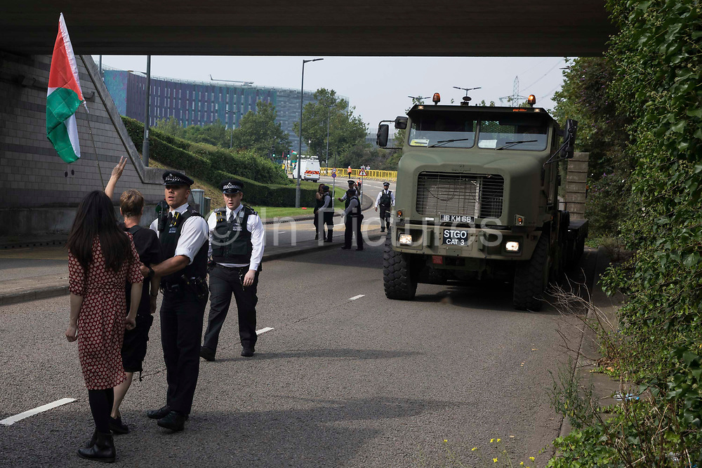 Human rights activists protest in front of a large military vehicle against the DSEI 2021 arms fair at ExCeL London on 6th September 2021 in London, United Kingdom. The first day of week-long Stop The Arms Fair protests outside the venue for one of the worlds largest arms fairs was hosted by activists calling for a ban on UK arms exports to Israel.