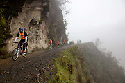 Travellers backpackers riding mountain bikes on 'the World's most dangerous road' down to Coroico in the Yungas, La Paz province, Bolivia.
