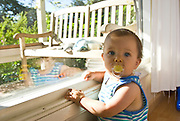 A nine-month old baby boy stands near a window, longing to go outside.