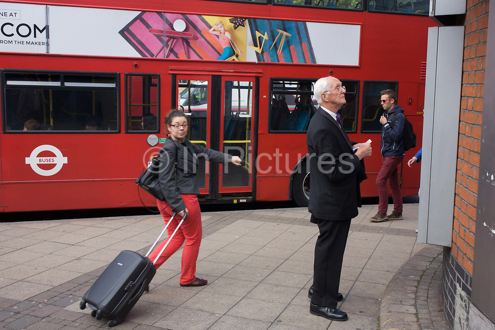 An elderly gentleman looks at a map of the city as London travellers make their way past at a Waterloo bus stop. The old man looks bewildered as a visitor to the capital, a confusing network of transport routes and locations that travellers need to understand during their travel day.