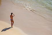 Woman in a Bikini Standing on the Beach