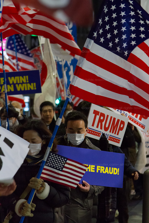 """Several hundred people, waving flags and banners, take part in a """"March For Trump"""" rally  in support of the out-going United States President, Donald Trump. Tokyo, Japan. Wednesday January 6th 2021. The rally of mostly Japanese people took place as part of a similar rally by Trump-supporters in Washington DC as the results of the 2020 US Presidential election were confirmed."""