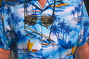 Seen in close-up detail, a holidaymaker's shirt is displayed in Magaluf. He has two pairs of spectacles hanging around his sunburned neck and a printed short-sleeved shirt depicting tropical paradise beach scenes with blue skies, palm trees and representing a Hawaiian Pacific Ocean scene with boats at sea, rolling on the waves. Magaluf is a popular holiday resort on the island of Mallorca, one of the Spanish Balearic Islands. A seedy resort very much orientated around British tourists and catering for both young parties as well as families, Magaluf is considered as an exotic alternative to the chilly seaside towns around the UK's coast.