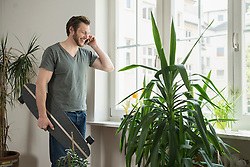 Mid adult man talking on mobile phone in living room, Munich, Bavaria, Germany