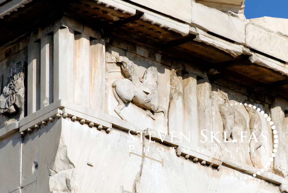 Acropolis. Athens. Greece. Close up view of the entablature of the south west corner of the world famous icon and landmark of Athens the Parthenon Temple which crowns the Acropolis summit. The Parthenon, a temple dedicated to the goddess Athena (Athena Parthenos), was constructed and decorated between 447 and 432 BC. The Parthenon is a Doric style peristyle temple with 17 fluted columns along each side and eight at the ends, which lean slightly inward and bulge out in the centre to cunningly offset the natural optical distortion. The entire Temple, apart from the roof,  were of white Pentelic marble with the sculptures that once decorated the pediments, friezes and metopes all being painted in vivid colours. The Parthenon was the centrepiece and jewel of the monumental rebuilding and transformation of the Acropolis during the time of Perikles. The Acropolis of Athens and its monuments are a UNESCO World Heritage Site.