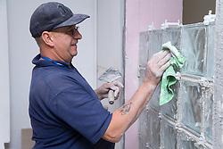 Man constructing glass brick window,