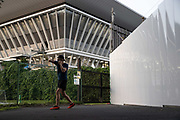 Nishimoto Seiho, a local resident, practices boxing outside Tokyo Aquatics Centre, a venue for swimming, diving and artistic swimming at the upcoming Tokyo 2020 Olympic Games, in Tokyo on July 21, 2021. - Since May 2021 when his go-to gym was closed due to the construction of Yumenoshima Park Archery Field, a venue for archery at the upcoming Tokyo 2020 Olympic Games, he has been working out at this location every night until the gym plans to re-open in October. (Photo by Yuki IWAMURA / AFP)